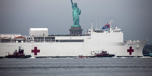 "The U.S. Navy hospital ship ""Comfort"" passes in front of the Statue of Liberty as it arrives in New York, U.S., on Monday, March 30, 2020. The naval hospital has 1,000 beds and 12 operating rooms. The Comfort will not treat Covid-19 patients, but rather handle overflow or acute trauma cases and other urgent needs, Acting Navy Secretary Thomas Modly told reporters at a briefing last week. Photographer: Michael Nagle/Bloomberg via Getty Images"
