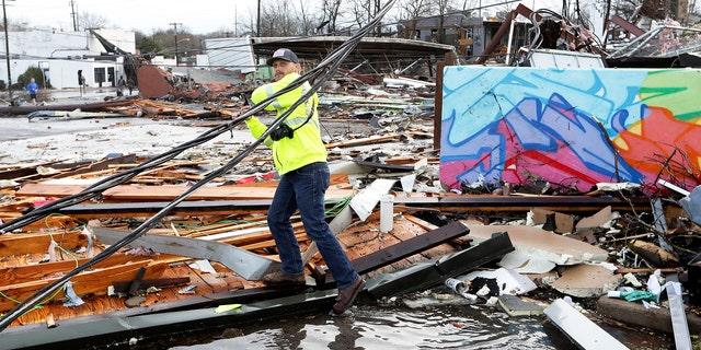 A man makes his way through debris following a deadly tornado Tuesday, March 3, 2020, in Nashville, Tenn.