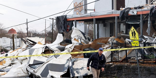 A man walks past storm debris following a deadly tornado, Tuesday, March 3, 2020, in Nashville, Tenn.