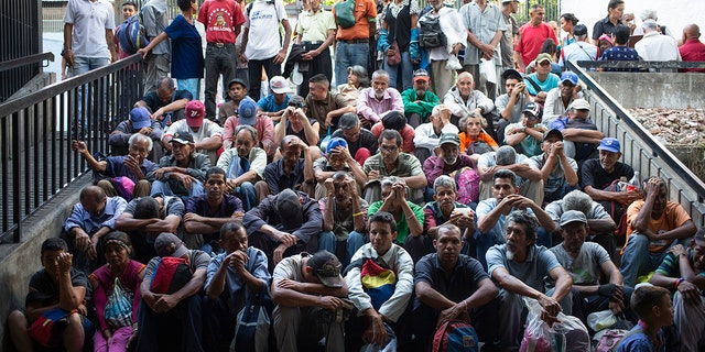 In this Feb. 27, photo, people wait outside of a religion center to receive a free meal in the slum called The Cemetery in Caracas. (AP Photo/Ariana Cubillos)