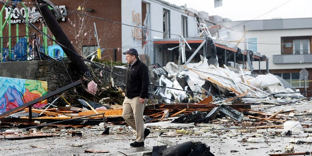 A man walks past storm debris following a deadly tornado Tuesday, March 3, 2020, in Nashville, Tenn.