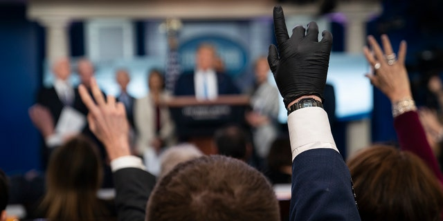 Reporters raise their hands to ask President Donald Trump questions during a press briefing with the coronavirus task force, at the White House, Monday, March 16, 2020, in Washington. (AP Photo/Evan Vucci)