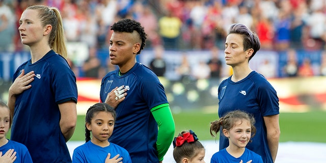 United States midfielder Samantha Mewis (3), goalkeeper Adrianna Franch, center, and forward Megan Rapinoe, right, stand with their jerseys turned inside out during the playing of the national anthem before a SheBelieves Cup women's soccer match against Japan, Wednesday, March 11, 2020 at Toyota Stadium in Frisco, Texas. (Associated Press)