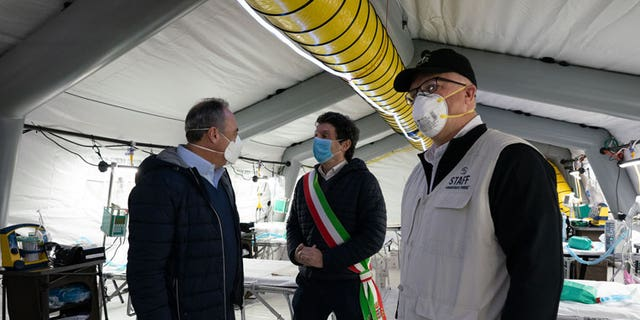 Lombardy Minister of Health Giulio Gallera, pictured left, and Cremona Mayor Gianluca Glamiberti, center, touring one of the eight tents that make up the medical facility.