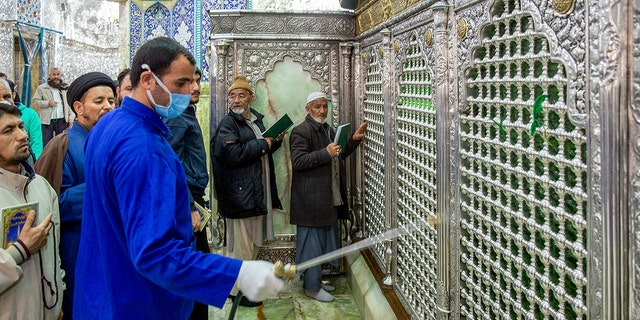 In this Monday, Feb. 24, 2020, photo, a man disinfects the shrine of Saint Masoumeh against coronavirus in the city of Qom 78 miles south of the capital Tehran, Iran.  (Ahmad Zohrabi/ISNA via AP)