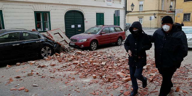 People walk past a damaged house after an earthquake in Zagreb, Croatia, Sunday, March 22, 2020. A strong earthquake shook Croatia and its capital on Sunday, causing widespread damage and panic.(Associated Press)