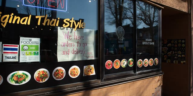 A sign indicating take out and delivery services are available is displayed in a window of a restaurant in the University District of Seattle, Wash., on March 18.