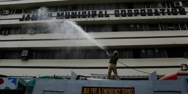 A fire brigade person disinfects a building during lockdown to prevent the spread of new coronavirus in Jammu, India, Tuesday, March 31, 2020.