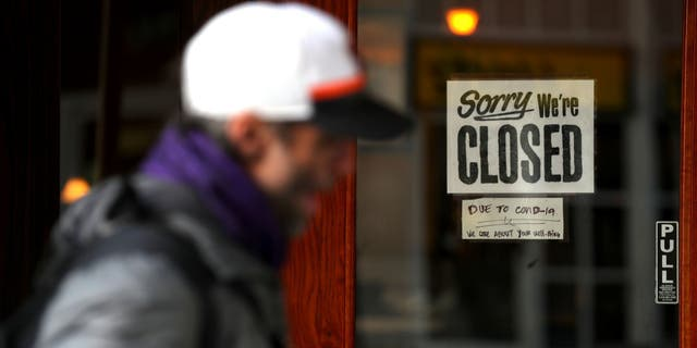A pedestrian walks by a closed sign on the door of a restaurant on March 17 in San Francisco.