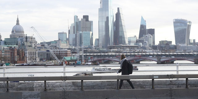 A commuter crosses an empty Waterloo Bridge in London on Tuesday after British authorities ramped up public health measures, telling people who are in the groups considered most vulnerable to severe COVID-19 illness to stay at home for three months. (Jonathan Brady/PA via AP)