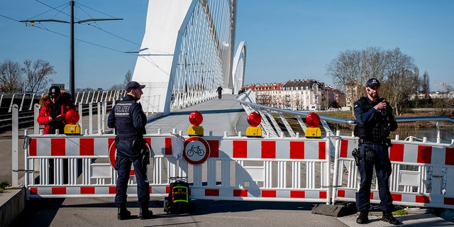 German police officers guard a closed bridge at the French/German border at the river Rhine in Kehl, Germany, Monday, March 16, 2020. German government allows only restricted access from France to Germany since Monday morning.  (AP Photo/Michael Probst)