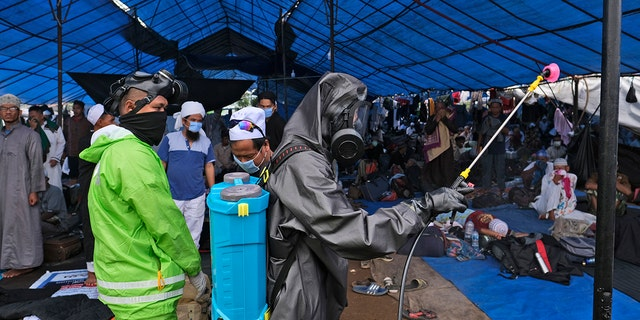 Paramilitary police officers in hazmat suit disinfect a tent built on a field where a mass congregation was supposed to be held in Gowa, South Sulawesi, Indonesia, on Thursday. (AP)