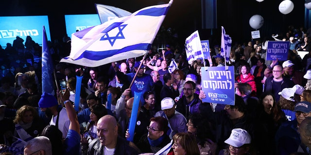 "Blue and White party supporters hold banners and flags during an election campaign rally in Tel Aviv, Israel, Saturday. The Hebrew writing says, ""Must to advance "". (AP Photo/Oded Balilty)"