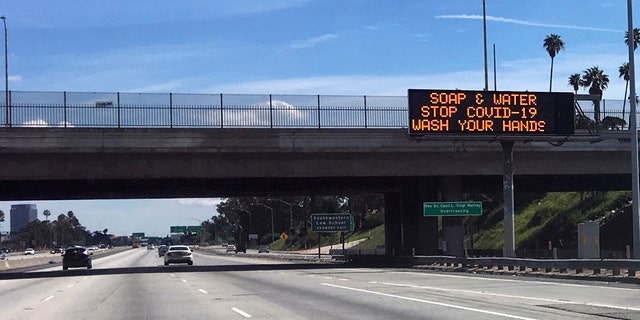 A Caltrans sign shows a pandemic health reminder on a sparsely traveled freeway in Los Angeles on Sunday. (AP Photo/John Antczak)