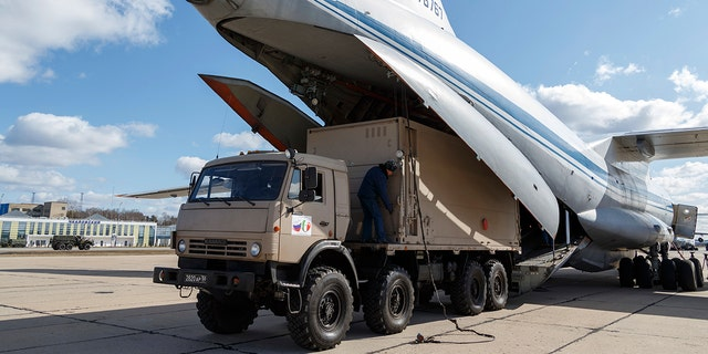 A military truck loads onto a Il-76 cargo plane in Chkalovsky military airport outside Moscow in preparation to deliver aid to Italy. (Alexei Yereshko, Russian Defense Ministry Press Service via AP)