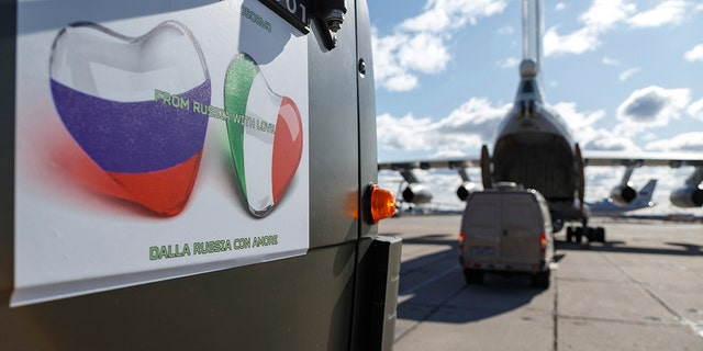 """A sign on a Russian military vehicle reads: """"From Russia with love"""" in several languages. (Alexei Yereshko, Russian Defense Ministry Press Service via AP)"""