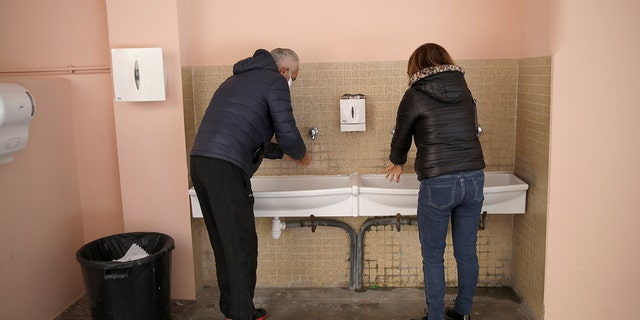 A couple wash their hands before voting Sunday March 15, 2020 in Menton, southern France. France is holding nationwide elections Sunday to choose all of its mayors and other local leaders despite a crackdown on public gatherings because of the new virus. For most people, the new coronavirus causes only mild or moderate symptoms. For some it can cause more severe illness. (AP Photo/Daniel Cole)
