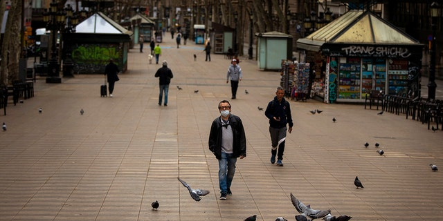 People walk along La Ramblas in Barcelona, Spain, Sunday, March 15, 2020. Spain's government announced Saturday that it is placing tight restrictions on movements and closing restaurants and other establishments in the nation of 46 million people as part of a two-week state of emergency to fight the sharp rise in coronavirus infections. (AP Photo/Emilio Morenatti)