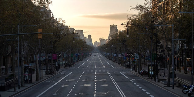 An avenue is seen empty in Barcelona, Spain, Sunday, March 15, 2020. Spain's government announced Saturday that it is placing tight restrictions on movements and closing restaurants and other establishments in the nation of 46 million people as part of a two-week state of emergency to fight the sharp rise in coronavirus infections. For most people, the new coronavirus causes only mild or moderate symptoms. For some, it can cause more severe illness, especially in older adults and people with existing health problems. (AP Photo/Joan Mateu)