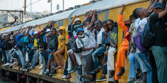 Train commuters hold on to the side of an overcrowded passenger train in Soweto, South Africa, Monday, March 16, 2020. South Africa will revoke nearly 10,000 visas issued this year to people from China and Iran, and visas will now be required for other high-risk countries that had been visa-free, including Italy and the United States. (AP Photo/Themba Hadebe)
