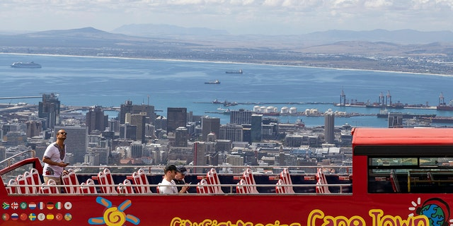 An open-air double-decker sightseeing bus stops on the slopes of Table Mountain, overlooking the city of Cape Town, South Africa, Friday, March 20, 2020  (AP Photo)