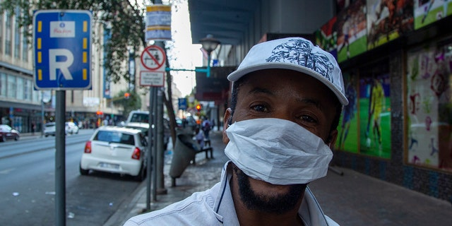 A man wears a face mask in downtown Johannesburg, South Africa, Friday, March 20, 2020.