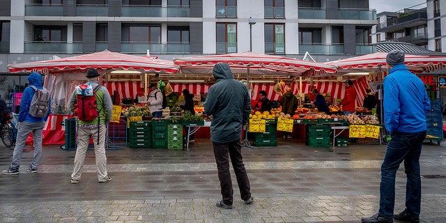People keep distance as they queue on a small weekly market in Frankfurt, Germany, early Saturday, March 21, 2020.