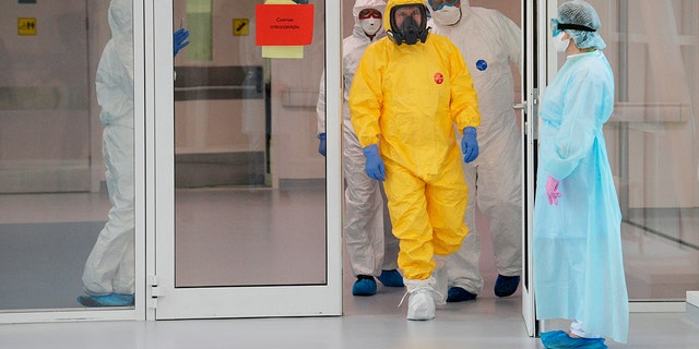 Russian President Vladimir Putin, center right, wearing a protective suit enters a hall during his visit to the hospital for coronavirus patients in Kommunarka settlement, outside Moscow, Russia, Tuesday, March 24, 2020.