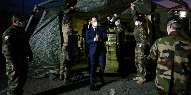 Macron wears a face mask during his visit at the military field hospital in Mulhouse on Wednesday. (Mathieu Cugnot/Pool via AP)