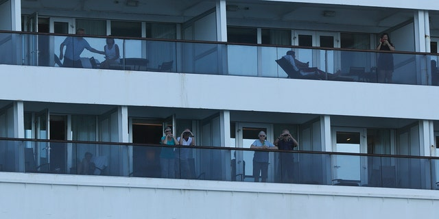 Passengers look out from the Zaandam cruise ship, anchored in the bay of Panama City. (AP Photo/Arnulfo Franco)