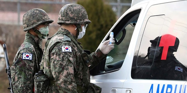 South Korean army soldiers wearing face masks check the temperature of a driver at a checkpoint of a military base in Daegu, South Korea on Wednesday, February 26. Military exercises between South Korean and American forces have been postponed over concerns about the virus. (Ryu Hyung-seok/Yonhap via AP)