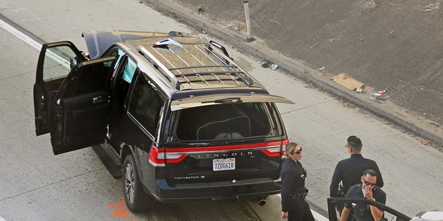 Los Angeles police officers stand after a pursuit of a stolen hearse with a casket and body inside on Interstate 110 in South Los Angeles last week. The hearse was stolen from outside a Greek Orthodox church in East Pasadena on Wednesday night. (AP Photo/Reed Saxon)