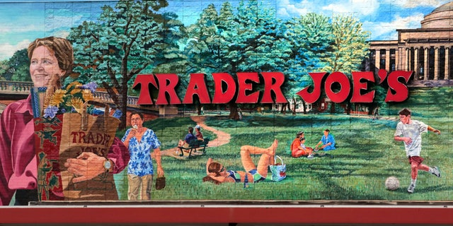 FILE - In this Aug. 13, 2019, file photo, Trader Joe's logo hangs on a mural at it's market in Cambridge, Mass.. The man who created Trader Joe's markets with a vision that college-educated but poorly paid young people would buy healthy foods if they could only afford them has died. Joe Coulombe's family says he died Friday at age 89. (AP Photo/Charles Krupa)