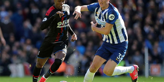 Brighton and Hove Albion's Dan Burn, right, and Crystal Palace's Wilfried Zaha in action during their English Premier League soccer match at the AMEX Stadium in Brighton, England, Saturday Feb. 29, 2020. (Gareth Fuller/PA via AP)