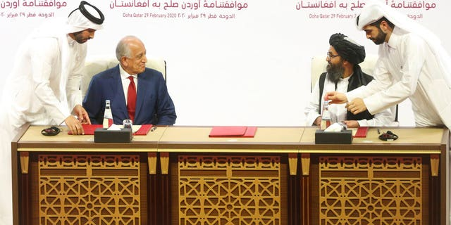 U.S. peace envoy Zalmay Khalilzad, left, and Mullah Abdul Ghani Baradar, the Taliban group's top political leader sign a peace agreement between Taliban and U.S. officials in Doha, Qatar, Saturday, Feb. 29, 2020. (AP Photo/Hussein Sayed)