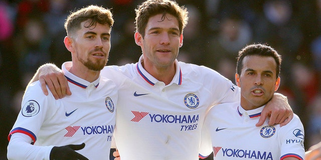 Chelsea's Marcos Alonso, centre, celebrates with team-mates Jorginho, left, and Pedro after scoring his side's first goal of the game against Bournemouth, in the English Premier League soccer match at the Vitality Stadium in Bournemouth, England, Saturday Feb. 29, 2020. (Mark Kerton/PA via AP)