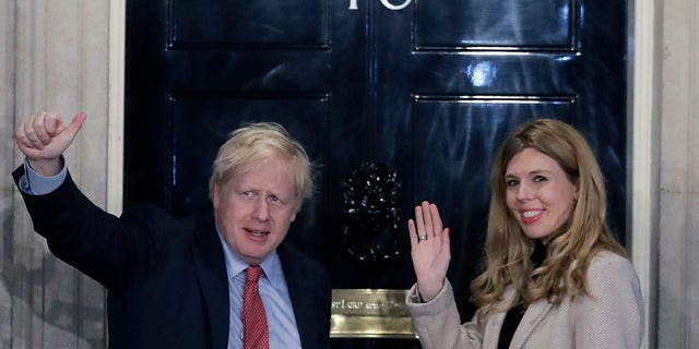 Britain's Prime Minister Boris Johnson and his partner Carrie Symonds wave from the steps of number 10 Downing Street in London, in December 2019. (Associated Press)