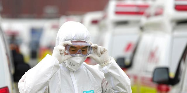 A health worker wearing a protective suit adjusts his goggles as he prepares to transport patients in Daegu, South Korea, Sunday, March 1, 2020. The coronavirus has claimed its first victim in the United States as the number of cases shot up in Iran, Italy and South Korea and the spreading outbreak shook the global economy.(Ryu Young-seok/Yonhap via AP)