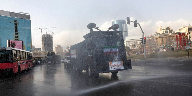 A police vehicle disinfects streets against coronavirus in Tehran, Iran, Sunday, March 1, 2020. While the new coronavirus has extended its reach across the world, geographic clusters of infections were emerging, with Iran, Italy and South Korea seeing rising cases. (AP Photo/Vahid Salemi)