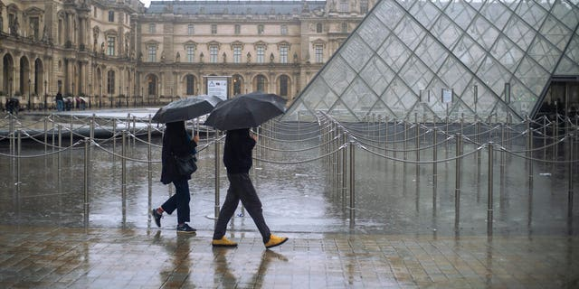 People walk by the Louvre museum, in Paris, France, Sunday, March 1, 2020. The spreading coronavirus epidemic shut down France's Louvre Museum on Sunday, with workers who guard its trove of artworks fearful of being contaminated by the museum's flow of visitors from around the world. (AP Photo/Rafael Yaghobzadeh)