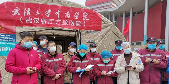 Medical workers attend a a morning conference outside a tent on the square in front of the Wuhan Living Room Temporary hospital in Wuhan in central China's Hubei province in this February photo.
