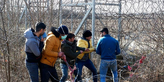 Migrants try to cut the fence at the Turkish-Greek border near the Pazarkule border gate in Edirne, Turkey on Monday, March 2, 2020. (AP Photo/Darko Bandic)