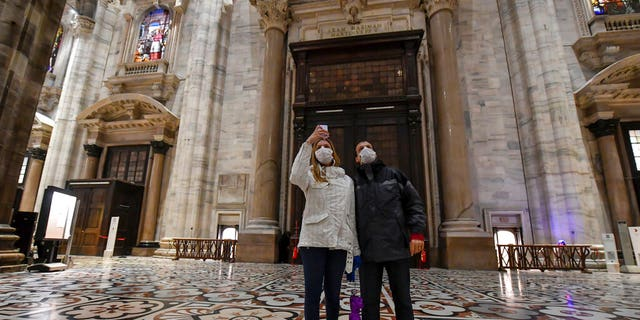 Tourits wearing face masks take pictures inside the Duomo gothic cathedral as it reopened to the public after being closed due to the COVID-19 virus outbreak in northern Italy, in Milan, Monday, March 2, 2020.