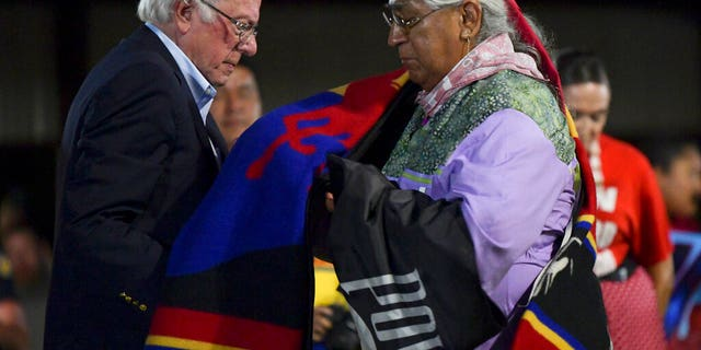 FILE - In this Sept. 22, 2019, file photo, Democratic presidential candidate U.S. Sen. Bernie Sanders receives an honor blanket from Cornel Pewewardy at the annual Comanche Nation Fair Powwow, in Lawton, Okla. Sanders hopes Super Tuesday, March, 3, 2020, in Oklahoma will be a repeat of his performance four years ago, while the rest of the Democratic field hope to get a foothold in the Sooner State as voters in 14 states head to the polls.(AP Photo/Gerardo Bello, File)