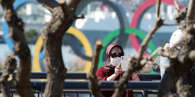 A tourist wearing a protective mask takes a photo with the Olympic rings in the background Tuesday, March 3, 2020, at Tokyo's Odaiba district. The spreading virus from China has put the Tokyo Olympics at risk. The Olympics are to open on July 24 - less than five months away. (AP Photo/Eugene Hoshiko)