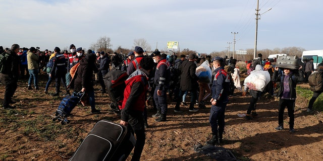 Migrants carrying their belongings pass next to Turkish policemen near the Pazarkule gate in Edirne region, at the Turkish-Greek border on Tuesday. A child died when a boat full of migrants heading to a Greek island capsized Monday, part of a wave of thousands trying to push through Greece's land and sea borders. (AP Photo/Darko Bandic)