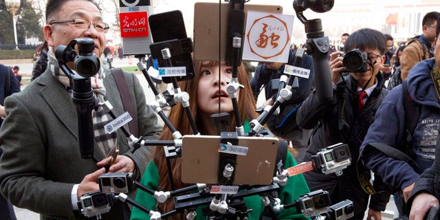 FILE: A Chinese journalist operates a harness with multiple recording devices capable of recording and multiple live streamings outside the Great Hall of the People where the opening session of the Chinese People's Political Consultative Conference (CPPCC) was held in Beijing, China.