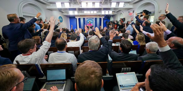 FILE: Journalists raise their hands in the White House press room during the daily briefing, in Washington.