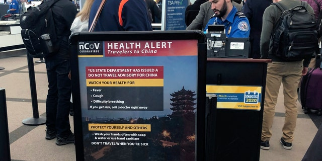 In this Monday, March 2 photo, a health alert for people traveling to China is shown at a TSA security checkpoint at the Denver International Airport. (AP Photo/Charles Rex Arbogast, File)