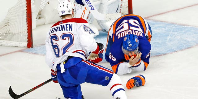 Montreal Canadiens left wing Artturi Lehkonen (62) watches as New York Islanders defenseman Johnny Boychuk (55) clutches his face after Lehkonen's skate hit him on the face during the third period of an NHL hockey game, Tuesday, March 3, 2020, in New York. The Canadiens won 6-2.